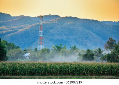 Telecommunication tower on the field with mountain background at sunset