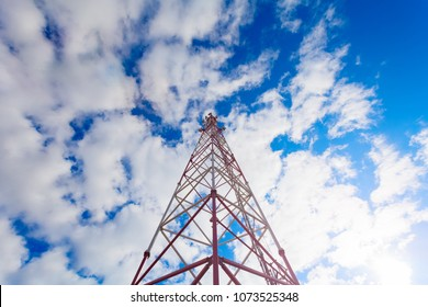 Telecommunication tower with panel antennas and radio antennas and satellite dishes for mobile communications 2G, 3G, 4G, 5G with red fence around tower against blue sky with clouds