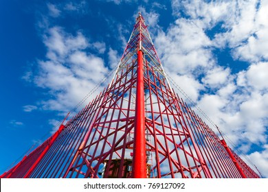 Telecommunication tower with panel antennas and radio antennas and satellite dishes for mobile communications (2G, 3G, 4G, 5G) with red fence around tower against blue with clouds