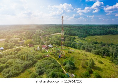 Telecommunication tower with  radio antennas and satellite dishes is installed on the rural on the green field with grass, bushes and trees. Concept of harmless of electromagnetic and microwav