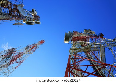 Telecommunication towers on blue sky.