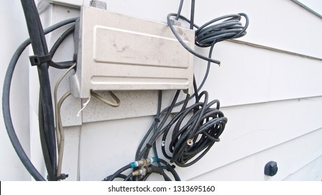 A telecommunications box with internet, phone and television subscription cables installed on the siding of a residential home.