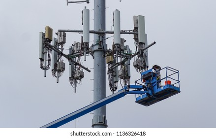 A telecommunications engineer in a crane performs maintenance work on a cellular antenna tower assembly in southern California.