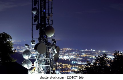 Telecommunications tower, antenna and satellite dish and city at night as background