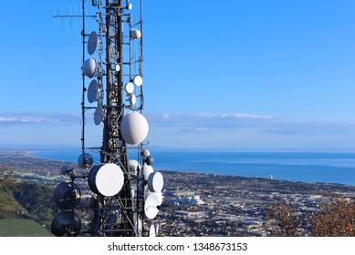 Telecommunications tower, antenna and satellite dish and coastline as background
