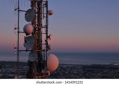 Telecommunications tower, antenna and satellite dish and aerial view of the city as background, sunset. Copy space