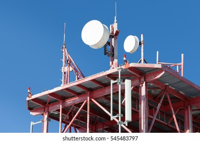 Telecommunications tower with antennas and clear blue sky on background