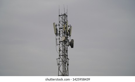 Telecommunications tower with cloudy sky background