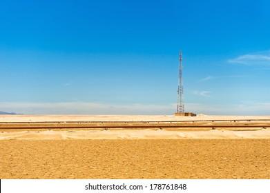 Telecommunications tower and oil pipeline in the Sahara desert, Egypt.