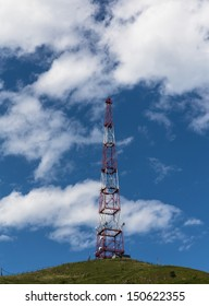 Telecommunications tower over blue sky.
