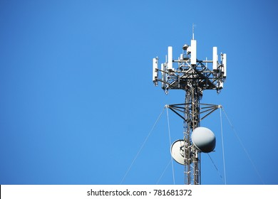 Telecommunications tower set against a blue sky with ample copy space. Also referred to as wireless communications tower.