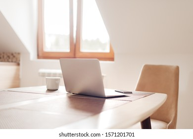 Telecommuting workspace with laptop and smartphone, selective focus