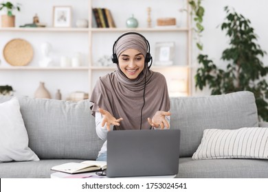 Teleconference. Smiling muslim woman having video call on laptop, talking with co-workers, gesturing at camera while sitting on couch in living room