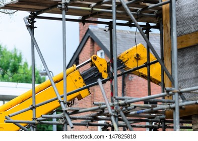 A telehandler lifts items during construction of a house