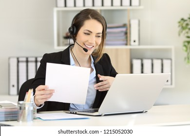 Telemarketer attending a call consulting online information in a laptop at office