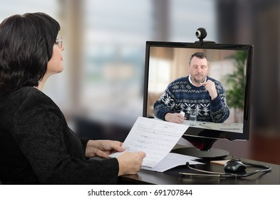 Telemedicine female doctor asks middle-aged man how does he feel receiving prescription medicine. Remote patient wearing colored sweater is seen in computer monitor holding white pill.
