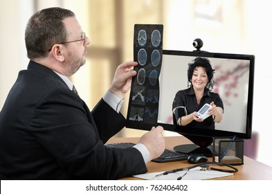 Telemedicine male doctor goes over brain x-rays image in front of virtual female patient in computer monitor. Positive mature woman has just measured blood pressure and shows outcomes to him
