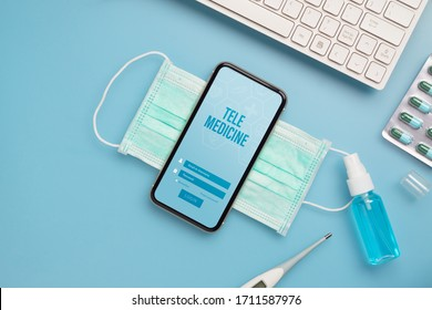Telemedicine online application background concept. Mockup mobile phone with facial masks, clinical thermometer, medicine tablet and Alcohol Mini Hand Sanitizer Spray.