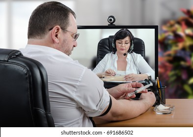 Telemedicine practitioner explains intravenous injection technique to middle aged businessman. Remote doctor uses training arm. Patient tries to repeat her manuals watching at computer monitor
