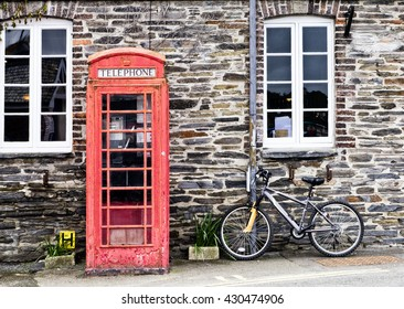 Telephone box and bicycle; Traditional UK red telephone box and bicycle in English village setting