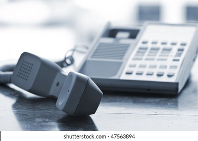 Telephone handset off the hook on desk