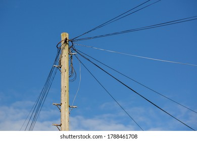 Telephone lines on a wooden pole or telegraph pole in a street heading off to different homes