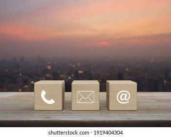 Telephone, mail, email address on wood block cubes on wooden table over blur of cityscape on warm light sundown, Business customer service and support online concept