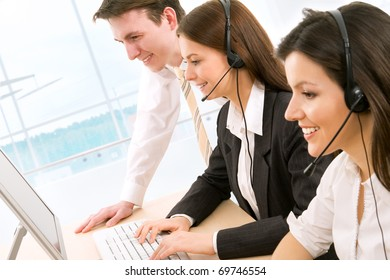 Telephone operators looking at the monitors and working