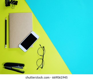 Telephone paper clip glasses pencil Stapler and book on yellow and blue background