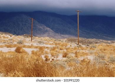Telephone poles in desert against dark mountains