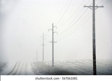 Telephone poles on road to nowhere, foggy snowstorm, Rocky Mountains,Idaho