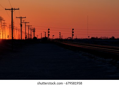 Telephone Poles and Railway Tracks in an Orange Sunset