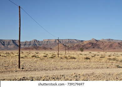 Telephone poles run through a rocky, desolate, mountainous landscape in the Namib Desert in Namibia, Africa.