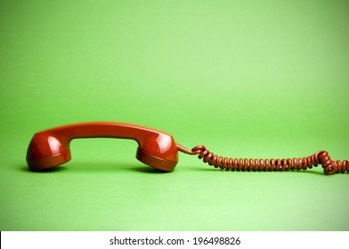 A telephone receiver and cord lying face down.