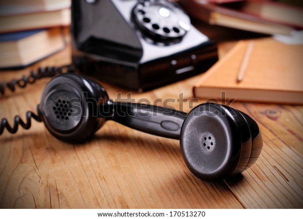 telephone receiver photographed in close-up on wooden table