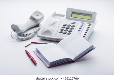 The telephone set, notepad and pen on a white background