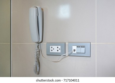 Telephone and socket on the wall in the hotel bathroom