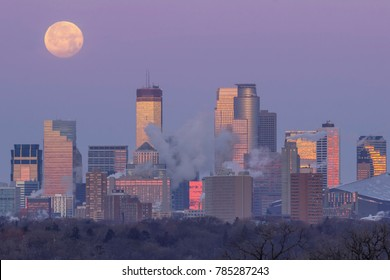 A Telephoto Close Up Compressing the Skyline of Minneapolis Reflecting the Sunrise as the Full Moon Sets Behind the City during the Morning Twilight