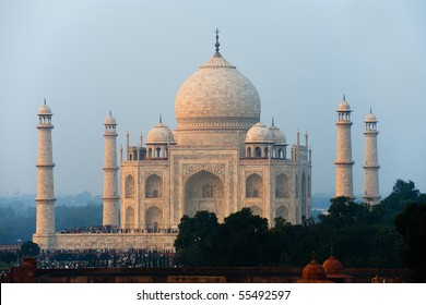 The telephoto distant Taj Mahal white marble reflects orange glowing sunset colors in the evening in Agra, India. Horizontal copy space
