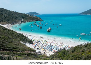 telephoto shot of the beautiful and famous prainhas beach in pontal do atalaia, arraial do cabo, rio de janeiro, brazil, the picture is shot through the native cactus of the place showing the locals