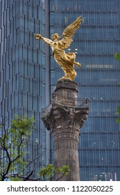 Telephoto shot of beautiful gold statue of Angel of Independence perched on top of monument column with high rise in background on cloudy day in Mexico City
