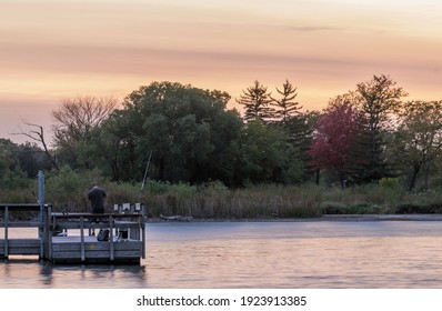 A Telephoto Shot of a Man Fishing from a Dock on Lake Haiwatha in South Minneapolis during a Vibrant Fall Golden Hour