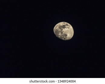 Telephotos of the moon at approximately 85% full in the clear night sky.