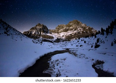 Peña Telera at night with snow, the sky full of stars, and the stream in the foreground