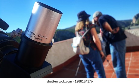 a telescope eyepiece, with people at the background observing the sun