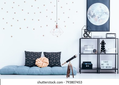 Telescope next to blue mattress with cushions in kid's bedroom interior with stars stickers and moon poster on white wall above shelves