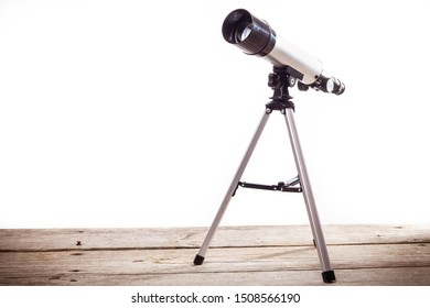 telescope on a white background laid on a rough wooden board