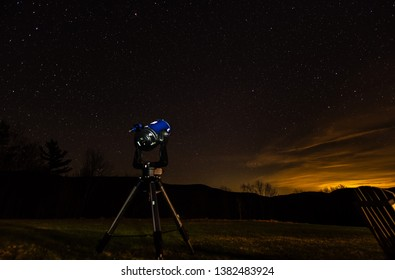 Telescope outdoors against starry sky