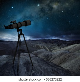 telescope tripod pointing the milky way in a desert landscape