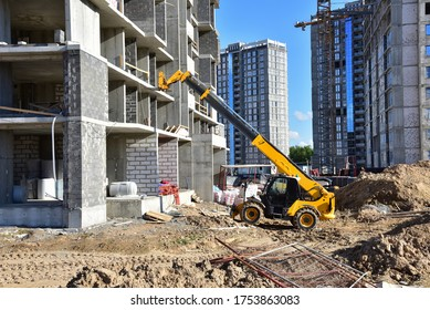 Telescopic handler work at the construction site. Construction machinery for loading. Tower crane during construct a multi-storey residential building. Wheel loader for lifting goods
